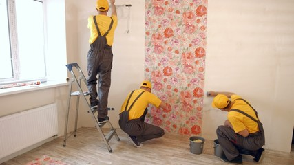 Brigade of builders hang wallpaper in the apartment.