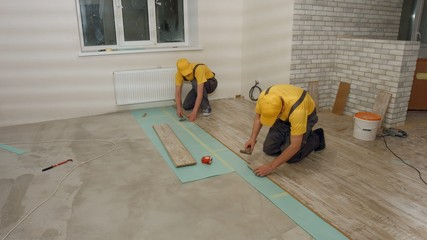 Brigade of workers laying  laminate. Laying laminate.