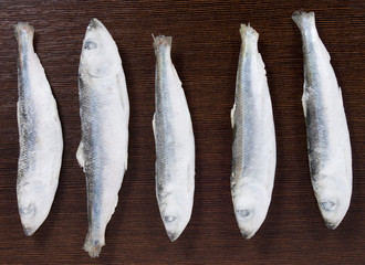 Five frozen sprats on a brown board background