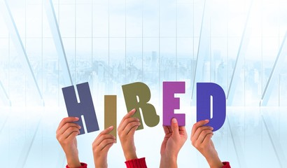 Composite image of hands holding up hired