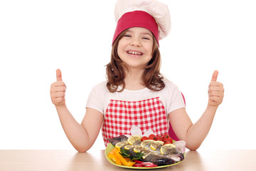 happy little girl cook with fish and thumbs up