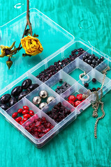 box of beads for needlework on wooden table