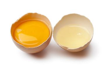 Egg yolk and white in a broken egg shell