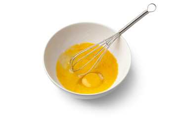 Beaten egg yolks in a bowl with whisk