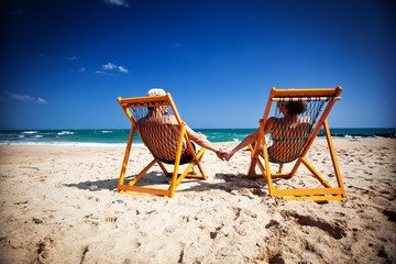 Couple sitting in beach chairs and holding hands on a tropical b