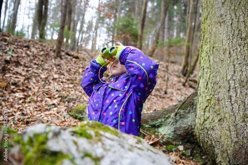 Girl looking through the binoculars - 80382353