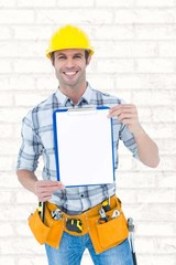 Composite image of confident carpenter holding clip board