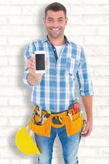 Smiling handyman showing mobile phone