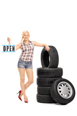 Woman holding an open sign next to a stack of tires