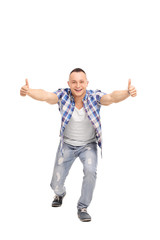 Joyful guy with an attitude, giving thumbs up
