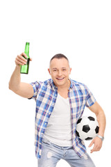 Young man holding a football and a beer bottle