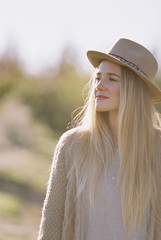 An apple orchard in Utah. Portrait of a woman with long blond hair, wearing a hat.