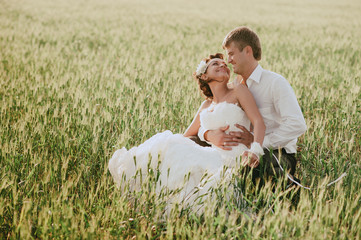 Bride and groom sit on the nature and looking at each other