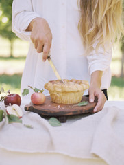 An apple orchard in Utah. Woman standing at a table with food, cutting an apple pie.