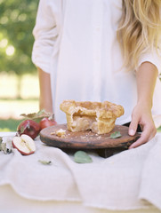 An apple orchard in Utah. Woman standing at a table with food, an apple pie.