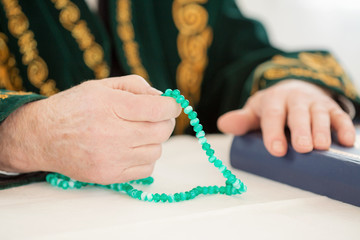 An old man's hand with rosary beads