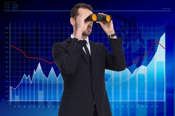 Elegant businessman standing and using binoculars