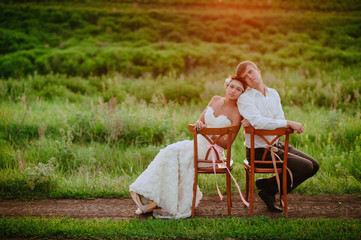 Beautiful young bride and groom  sitting on a chair