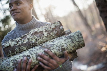 Man carrying firewood in forest in autumn.