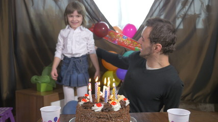 Man blowing candles on a birthday cake with his daughter