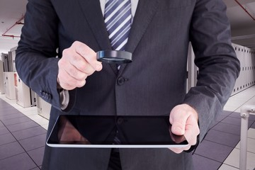 Businessman looking at tablet with magnifying glass