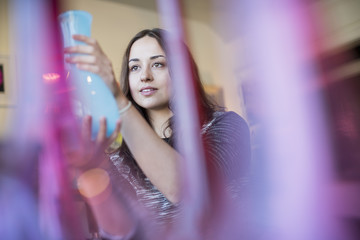 Woman holding a blue glass vase. Red and pink vases in the foreground.