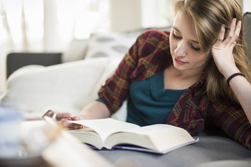 Young woman sitting on a sofa, reading a book.