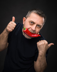 elderly man with red pepper in his mouth