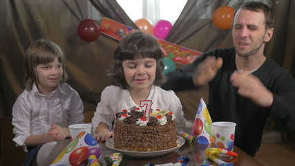 Young girl blowing candles on a birthday cake with her father