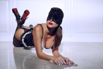 Sexy woman in lace eye cover kneeling on floor
