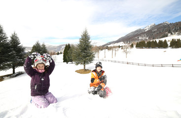 brother and sister playing in the snow in the mountains in winte