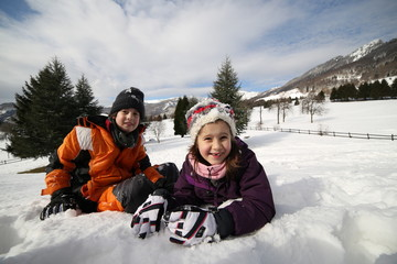 brother and sister playing in the snow in the mountains