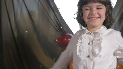 Young beautiful girl dancing at a birthday party with confetti
