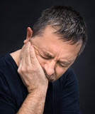 Toothache. Man with face closed by hand
