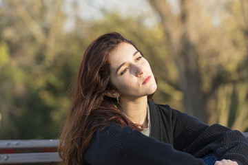Pensive beautiful young woman in the park looking away.