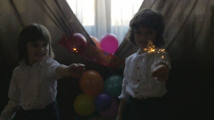 Young beautiful sisters playing with fireworks - birthday party