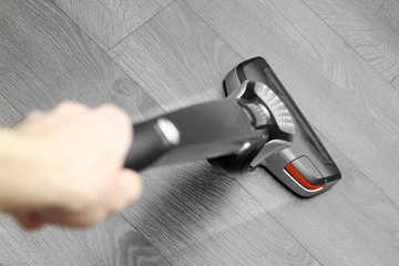 cleaning floor with cordless vacuum cleaner