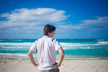 Handsome young man  against bright beach background, relaxes