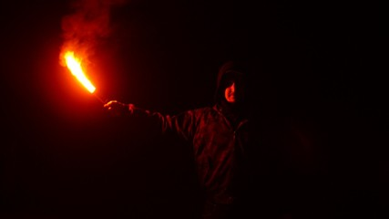 Man holding red bengal fire