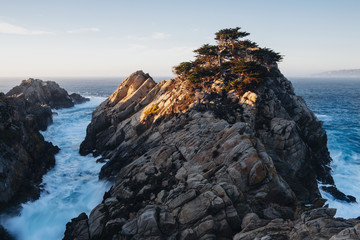 Dramatic cliffs and coastline at dusk in the Point Lobos State Reserve on the Pacific coastline. White foaming water.