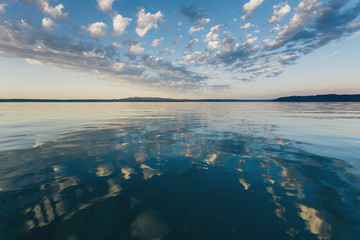 Dramatic clouds and sky reflecting over calm ocean water at dusk, Hood Canal water channel near Puget Sound.