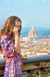 Woman talking cell phone against panoramic view of florence