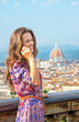 Happy young woman talking cell phone in florence