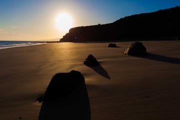 Rocks on a sandy beach sunset