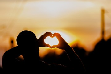 Sunset. Silhouette hand in heart shape with sunrise in the