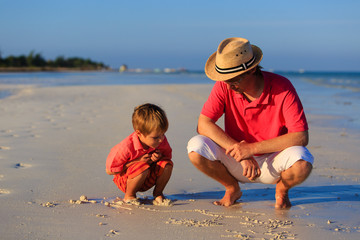 father and son drawing on summer beach