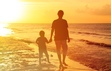 father and son walking at sunset sea