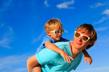 Father and little son playing on blue sky