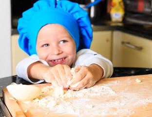 happy little boy kneading dough
