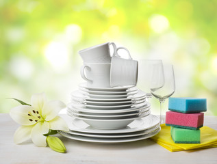 Clean tableware, dishwashing sponges and lily flower